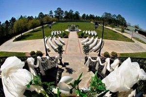 A view from the second floor of The Manor, a wedding venue near Lafayette, Louisiana, showing chairs setup for an outdoor wedding around the fountain.