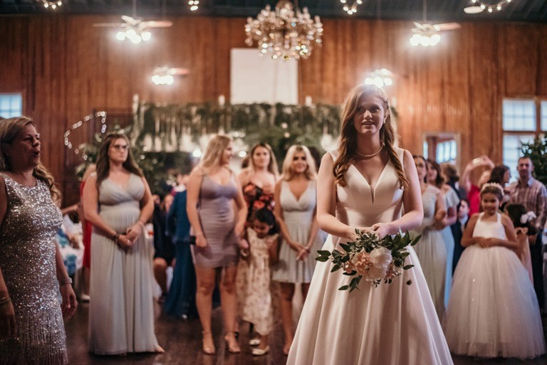 A bride throwing her bouquet at The Madison, a wedding venue located near Lafayette, Louisiana.