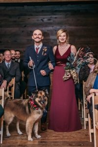 A dog walking down the aisle at a wedding.